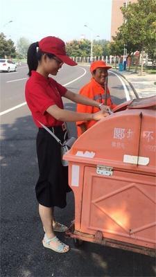 志愿者帮助环卫工人收拾垃圾。