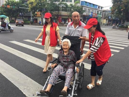 志愿者帮助行动不便的老人过马路