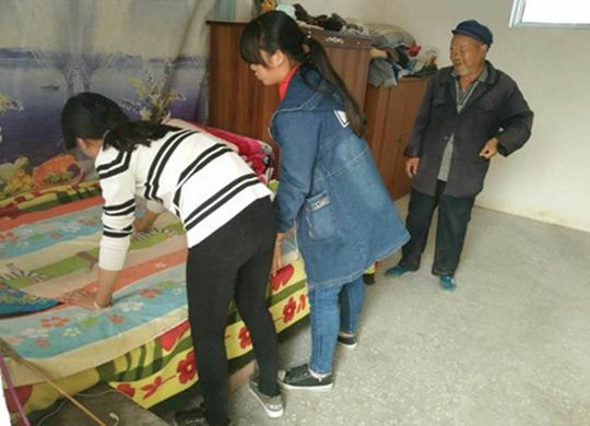 学生帮老人整理床铺