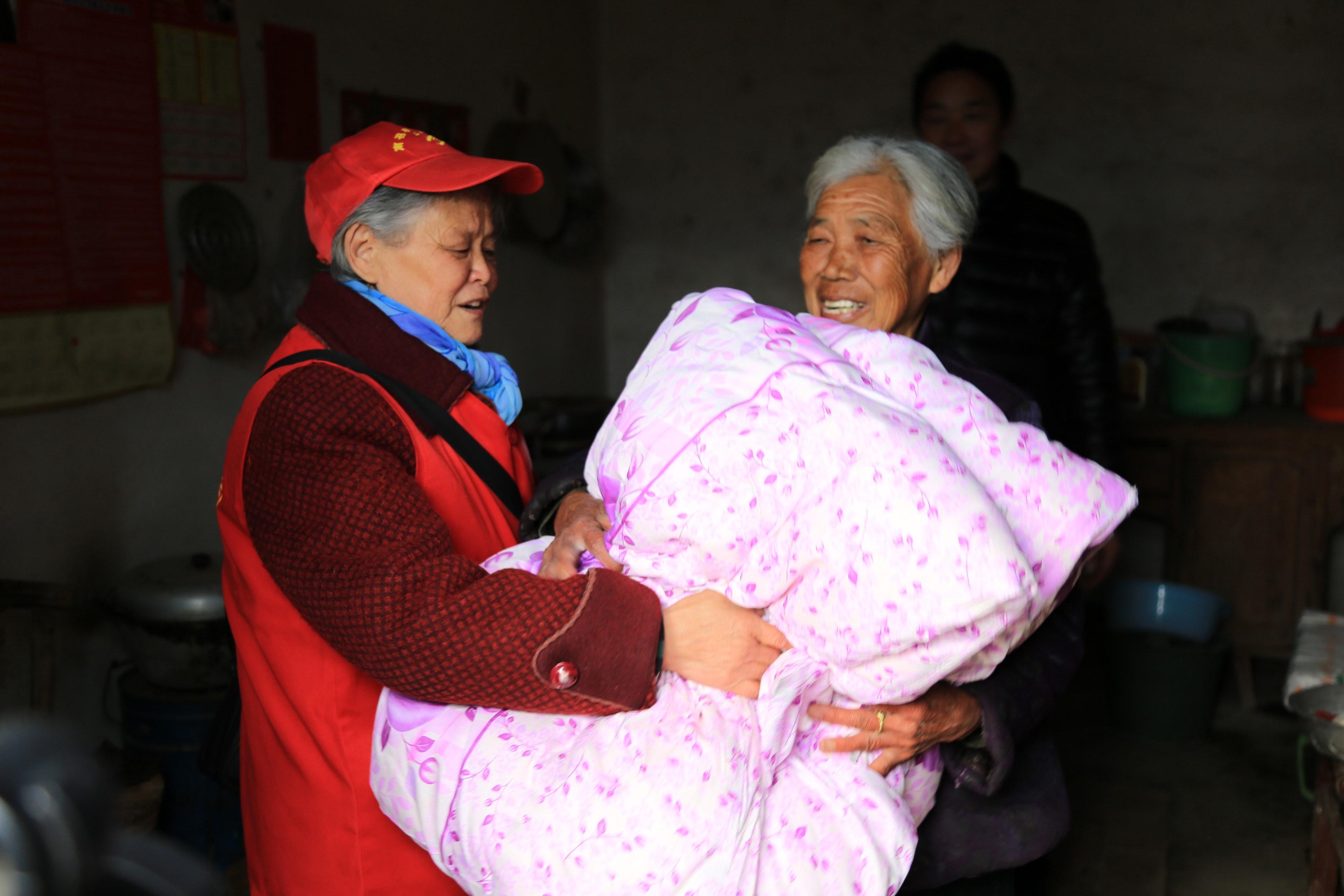 南召县爱心家园志愿者协会会长杜文兰为贫困家庭、孤寡老人送棉被。