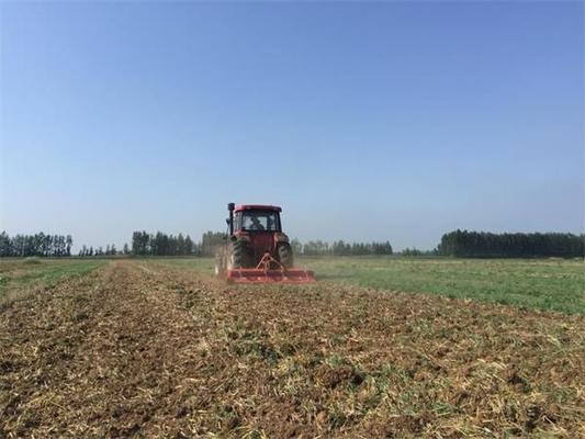 开源农业公司农机手在田间耕作整地。