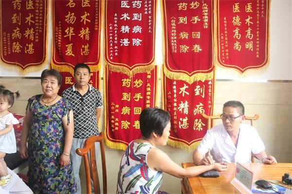 11。舞阳县中医院大夫贺全中,正在给病人把脉看病。