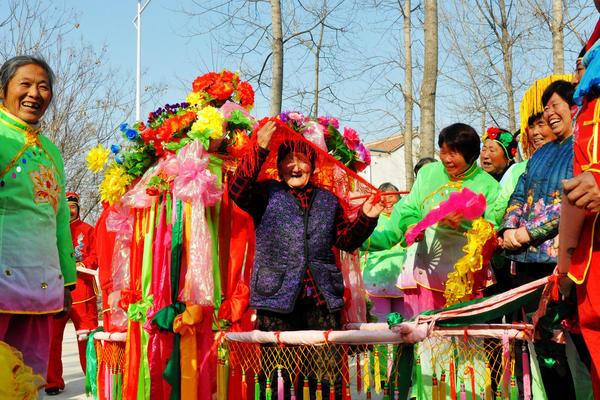 """自从村里建好文化广场后,群众有了娱乐的场所,图为冯塘乡刘庄村96岁的老奶奶在家门口体验""""坐花轿""""。   杜欣   摄"""