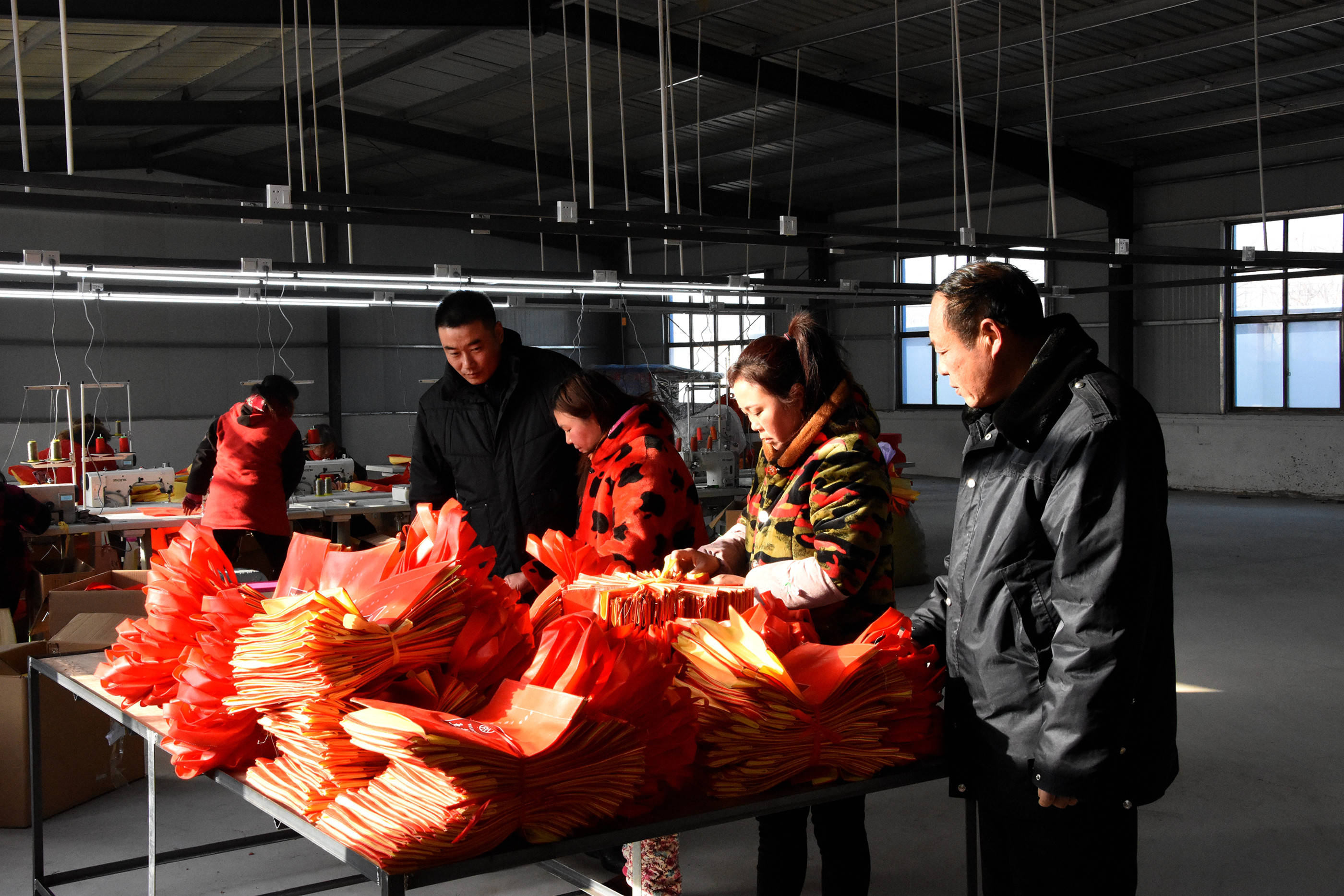 在临蔡镇黄楼行政村扶贫车间,村民正在紧张地赶制一批代加工手提袋。袁祥金摄