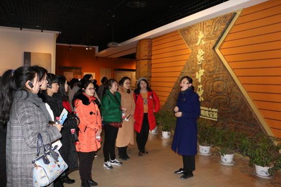 图为该公司女职工正在聆听解说员讲解河南古代文明瑰宝展