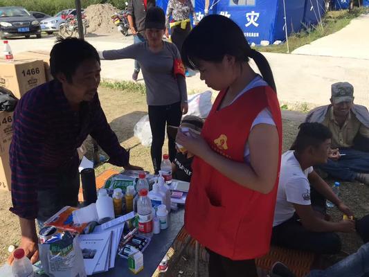 图为王秀娟同学为灾民处理外伤、配发药品 (2)