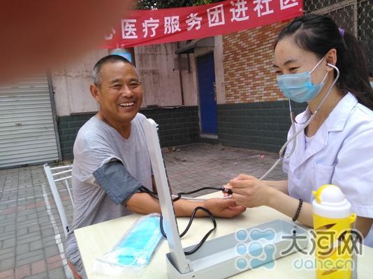 志愿者为居民测量血压 胡婧
